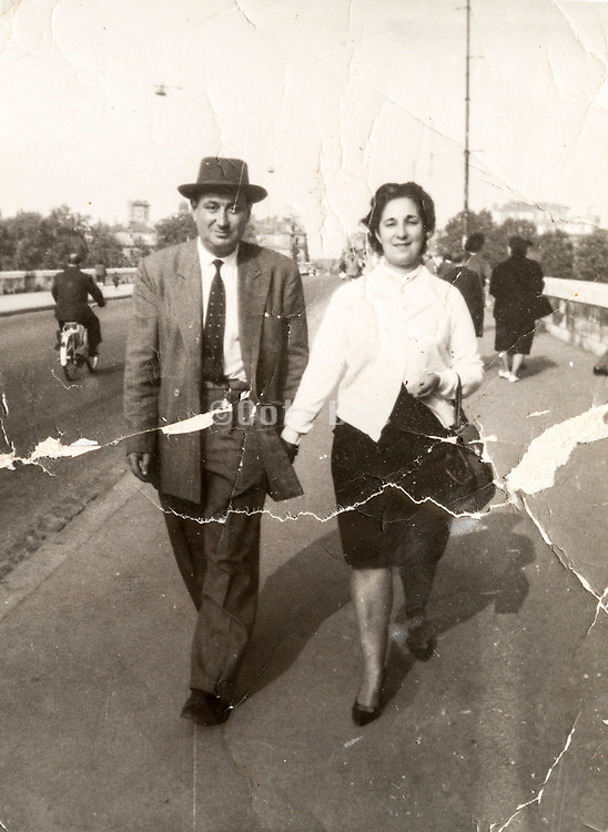deteriorating photo of couple walking over a bridge France 1960