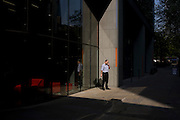 A city worker pauses outside his office building in sunshine for a cigarette and call on his smartphone.
