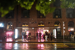 © Licensed to London News Pictures. 03/10/2020. Manchester, UK. People shelter from rain in bus stops in Stevenson Square at 10pm . Pubs, bars and clubs close at 10pm in Manchester City Centre in order to comply with measures introduced to combat the spread of Coronavirus. Photo credit: Joel Goodman/LNP