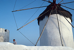 Man next to a windmill in Mykonos, Greece