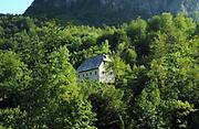 stone farmhouse with a shingled roof above the Blue Eye of Kapre,  Syri i Kalter i Kaprese, a blue river pool. Teth, Tethi, Albania.