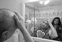 MIDDLEBURY, CT - 24 DECEMBER 2007 -112008JT48-.Marie Tyrrell looks at herself in the mirror after her daughter Tracie Marcil shaved her head on Christmas Eve 2007 at Marie's house in Middlebury. In her fourth round of chemotherapy, this was the second time Marie shaved her head since being diagnosed with lung cancer in 2006..Josalee Thrift / Republican-American