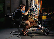 Graduate student Dan Paluska adjusts mechanisms of the lower torso and extremity robot, called M2. The robot is funded by a DARPA (US Defense Advanced Research Projects Agency) program called Tactile Mobile Robotics. DARPA's goal is to replace soldiers and rescue workers in dangerous situations. MIT Leg Lab, Cambridge, MA.