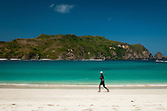 Indonesia, Lombok. Man walking on the beautiful Mawun Beach near Kuta. Probably he's a fisherman coming back from his daily catch.