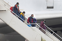 © Licensed to London News Pictures. 31/01/2020. Brize Norton, UK. Passengers and medical staff disembark from a charter plane at RAF Brize Norton after being evacuated from Wuhan, China. The flight, carrying 83 Britons and 27 foreign nationals from the centre of the coronavirus outbreak, was initially delayed because of a lack of clearance by Chinese Authorities. The British passengers will travel by coach to a hospital in the north west of England for 14 days quarantine. Photo credit: Peter Macdiarmid/LNP