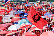 """26 MARCH 2009 -- BANGKOK, THAILAND: A supporter of deposed Thai Prime Minister Thaksin Shinawatra waves a flag with Che Guevara's photo on it during a demonstration in favor of returning Thaksin to power. More than 30,000 members of the United Front of Democracy Against Dictatorship (UDD), also known as the """"Red Shirts""""  and their supporters gathered on Sanam Luang (the vast open field in front of the Palace) and descended on central Bangkok March 26 to start a series of protests against and demand the resignation of current Thai Prime Minister Abhisit Vejjajiva and his government. The protest is a continuation of protests the Red Shirts have been holding across Thailand. Thaksin was deposed in a coup and went into exile rather than go to prison after being convicted on corruption charges. He is still enormously popular in rural Thailand.  PHOTO BY JACK KURTZ"""