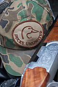 Ducks Unlimited and organisation which brings together duck hunters from all over the US, is promoted through this symbol seen on a hat near Minot, North Dakota, United States. The logo can be seen on baseball / hunting caps and bumper stickers everywhere you go here in the duck hunting state of North Dakota. The engraved stock of a double barrel shotgun sits ready should any fair game be seen.