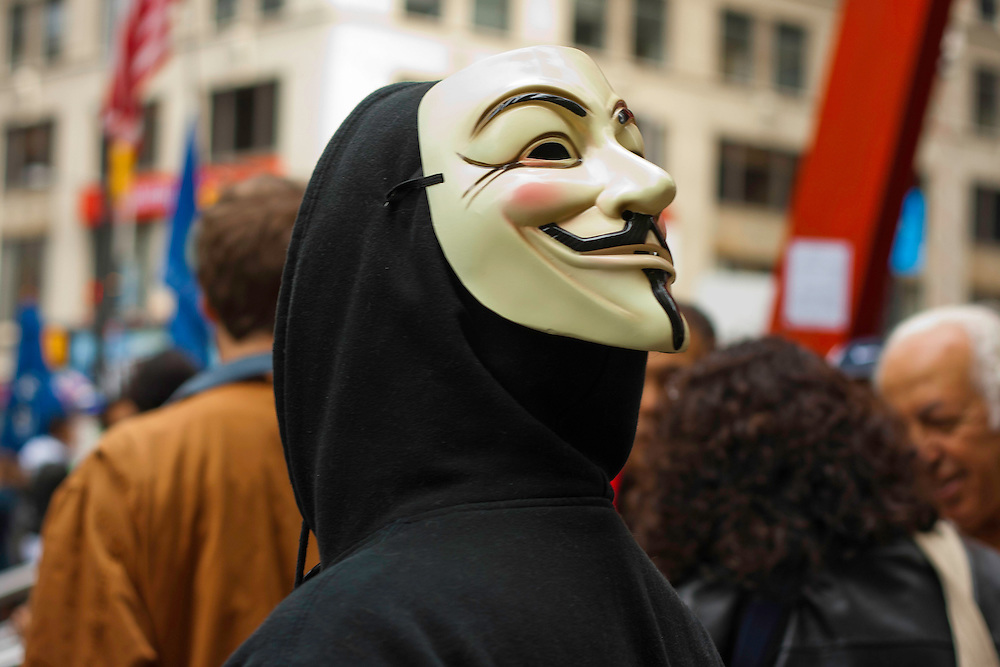 Protester wearing a Guy Fawkes mask looks on at an interview in progress in Zuccotti Park. October 21, 2011.