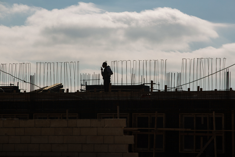 The silhouette of a Palestinian construction worker smoking a cigarette is seen at a construction site in Givat HaTamar neighborhood of the West Bank Jewish settlement of Efrat in the Gush Etzion settlement bloc, which is situated on the southern outskirts of the Palestinian West Bank city of Bethlehem, on December 30, 2016.