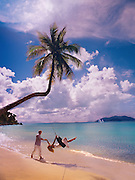 A young couple spends romantic time together on a palm tree tire-swing on the British Virgin Islands