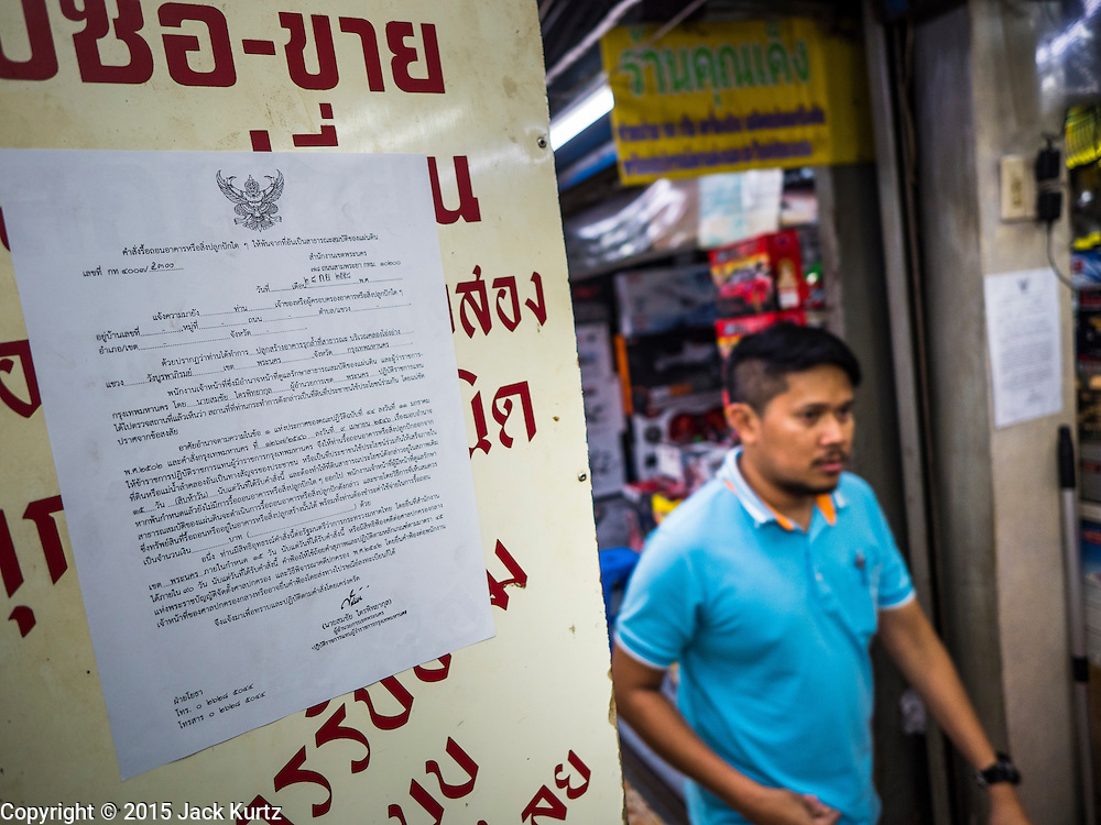 29 SEPTEMBER 2015 - BANGKOK, THAILAND:  A man walks past a flyer on a wall announcing the closure of Saphan Lek market. Street vendors and illegal market vendors in the Saphan Lek area will be removed in the next two weeks as a part of an urban renewal project coordinated by the Bangkok Metropolitan Administration. About 500 vendors along Damrongsathit Bridge, popularly known as Saphan Lek, have 15 days to relocate. Vendors who don't move will be evicted. Saphan Lek is just one of several markets and street vending areas being closed in Bangkok this year. The market is known for toy and replica guns, bootleg and pirated DVDs and CDs and electronic toys.   PHOTO BY JACK KURTZ