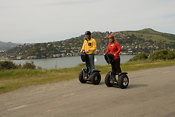 Couple on Segways, each on a Segway, on Angel Island State Park in San Francisco Bay, California, CA. Model released..Photo camari204-70412..Photo copyright Lee Foster, www.fostertravel.com, 510-549-2202, lee@fostertravel.com.