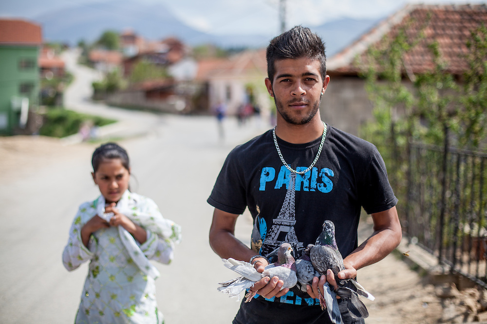 Young Roma man from the local Roma community is holding pidgeons in his hands while getting a portrait during the European Immunization Week in the city of Vinica in Macedonia.