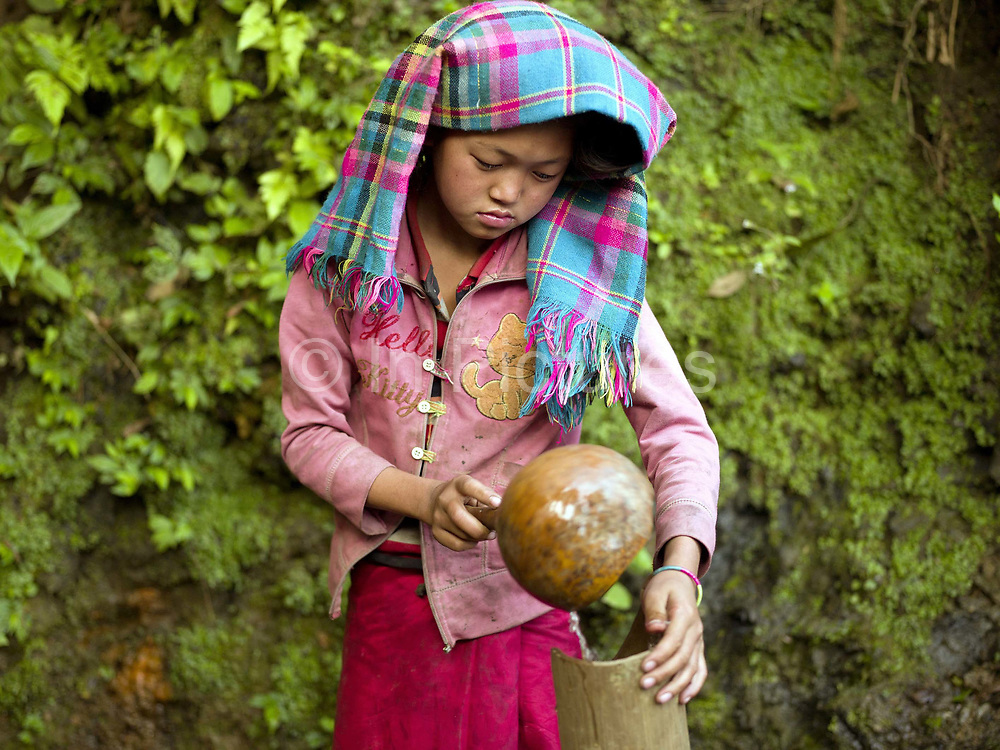 In the remote and roadless Akha Nuquie ethnic minority village of Ban Chakhampa, Phongsaly Province, Lao PDR, young girls first task of the day is collect water using a gourd scoop and carry it back to the village in traditional bamboo water carriers. Although there is a small basic school in Ban Chakhampa, it is still rare for girls in such remote villages to go to school because they are required to help their families with jobs at home.