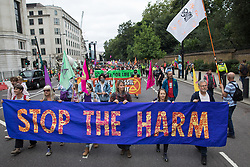 London, UK. 26th August, 2021. Environmental activists from Extinction Rebellion, Stop HS2, XR Roads Rebellion and Paid to Pollute take part in a Stop The Harm march during the fourth day of Impossible Rebellion protests. Extinction Rebellion are calling on the UK government to cease all new fossil fuel investment with immediate effect.