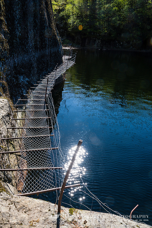 Norway, Sokndal, Løtoft. Bridge made of iron poles drilled into the cliff side.