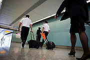 Arriving British Airways flight deck and cabin crew stride through arrivals after long-haul flight to Heathrow Airport's T5
