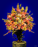 A colorful cut flower bouquet adorns a vase atop a marble pedestal at the annual Boston Flower show.