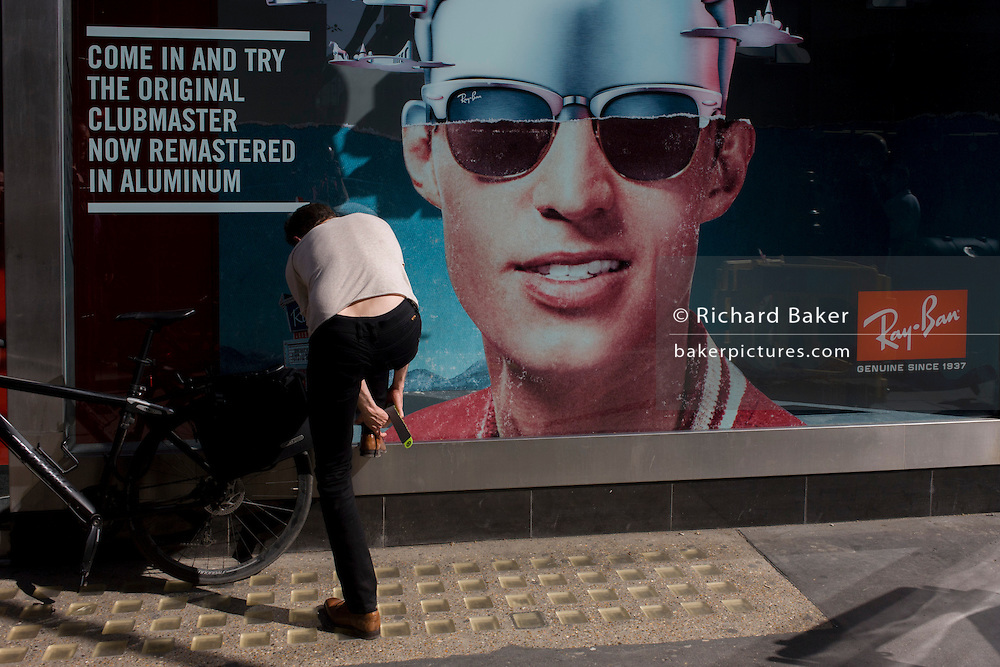 A cyclist stoops to fix leg protectors alongside a poster of a model showing stylish shades outside a sunglasses shop window selling Ray Bans on Long Acre in London's Covent Garden.