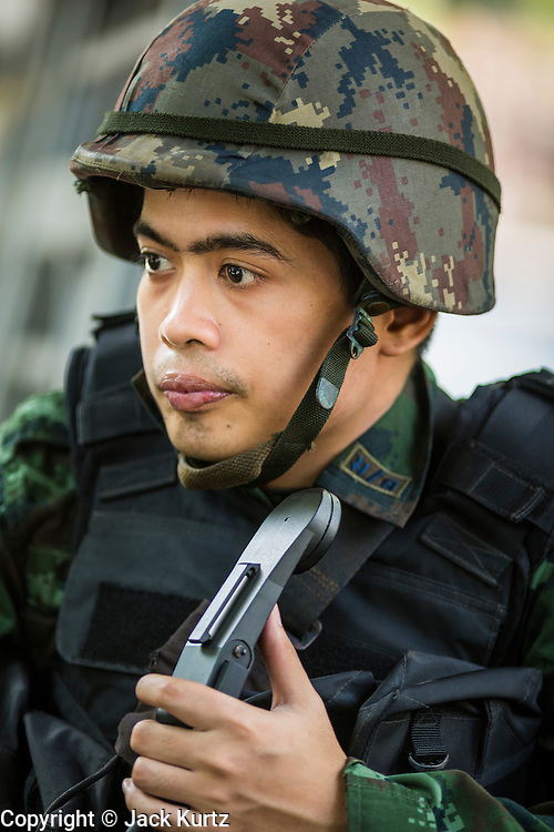 """20 MAY 2104 - BANGKOK, THAILAND:  A Thai soldier with a radio at a checkpoint on Rama I Road in Bangkok. The Thai Army declared martial law throughout Thailand in response to growing political tensions between anti-government protests led by Suthep Thaugsuban and pro-government protests led by the """"Red Shirts"""" who support ousted Prime Minister Yingluck Shinawatra. Despite the declaration of martial law, daily life went on in Bangkok in a normal fashion. There were small isolated protests against martial law, which some Thais called a coup, but there was no violence.  PHOTO BY JACK KURTZ"""