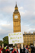 At the Climate Rush demonstration a climate change campaigner holds her placard 'Climate Action Now' in front of the House of Parliament.