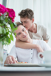 Homosexual couple having breakfast together, smiling