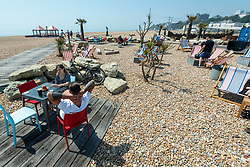 © Licensed to London News Pictures. 20/07/2021. FOLKESTONE, UK.  People on the shingle beach enjoying the sunshine in Folkestone.  The heatwave continues with temperatures in the upper 20sC.  Photo credit: Stephen Chung/LNP