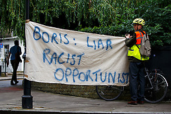 "© Licensed to London News Pictures. 30/06/2016. London, UK. A protester with a banner reads ""BORIS: LIAR, RACIST, OPPORTUNIST"" standing outside former Mayor of London Boris Johnson's house before leaving his house in London ahead of a press conference to make his bid to be next Conservative leader and UK Prime Minister on 30 June 2016. Photo credit: Tolga Akmen/LNP"