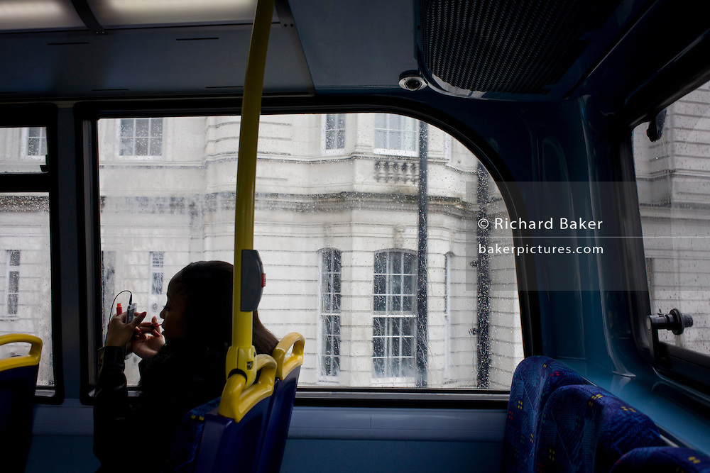A lone young woman applies lipstick using her smartphone as a mirror during a London bus journey.