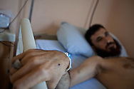 An injured Free Syrian Army (FSA) soldier sits in hospital in Antakya, Turkey, where he is receiving treatment for gunshot wounds near Lattakia, Syria. 12/06/2012