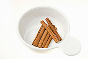 Whole Cinnamon sticks the bark of the Cinnamomum verum tree on white background