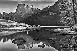 A fly-fisherman becomes part of the grand landscape at Green River Lake in the Wind River Mountains of Wyoming.  A black and white study.