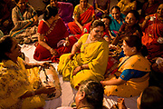 At a Hindu wedding the bride's relatives and friends sit together as they sign  marriage songs to the accompaniment of a dholak, a drum. Jaipur, India