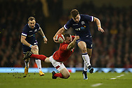 Huw Jones of Scotland © breaks past a tackle from Ken Owens of Wales  in the 1st half. Wales v Scotland, NatWest 6 nations 2018 championship match at the Principality Stadium in Cardiff , South Wales on Saturday 3rd February 2018.<br /> pic by Andrew Orchard, Andrew Orchard sports photography
