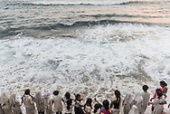 Colombo, Sri Lanka - March 29, 2017: Two teachers stand with a group of girls, all students and from more than one religion, and feel the waves lap their feet at the beach at Galle Face Green in Colombo, Sri Lanka.