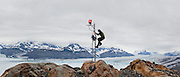 U. S. Geological Survey glaciologist Shad O'Neel climbs up an instrument tower to service a time-lapse camera installed at Columbia Glacier, Alaska.