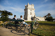 Couple and their bycicles with Belém Tower on the background. The Tower was classified as a UNESCO World Heritage Site in 1983 and included in the registry of the Seven Wonders of Portugal in 2007. It was built in the early 16th century and is a prominent example of the Portuguese Manueline style.