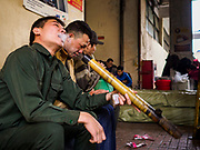 "22 DECEMBER 2017 - HANOI, VIETNAM:  Men spoke a traditional Vietnamese pipe in the wholesale clothes and fabric section of Dong Xuan Market in the old quarter of Hanoi. The old quarter is the heart of Hanoi, with narrow streets and lots of small shops but it's being ""gentrified"" because of tourism and some of the shops are being turned into hotels and cafes for tourists and wealthy Vietnamese.   PHOTO BY JACK KURTZ"