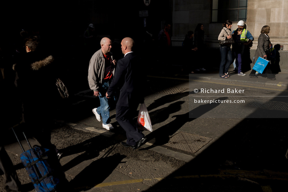 Bald-headed men seemingly clash in a shaft of early spring light in a side street in the capital's financial district. This is Lombard Street, originally a piece of land granted by King Edward I to goldsmiths from the part of northern Italy known as Lombardy (larger than the modern region of Lombardy). It is a narrow and usually dark sidestreet near the Bank of England in the heart of what is called the Square Mile - the inner-part and oldest quarter of London occupied first by the Romans 2,000 years ago. Nowadays the City of London is home to banks and financial institutions but also with a resident population of under 10,000 but a daily working population of 311,000.