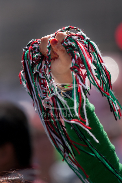 London, August 9th 2014. Wristbands made of the Palestinian colours are offered to the tens of thousands marching for Palestine in London.