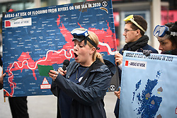 © Licensed to London News Pictures. 05/12/2019. London, UK.  Extinction Rebellion (XR) activists stage an action outside Shepherds Bush Tube Station highlighting climate change and flood risks to London. The group intends to ride the underground predicting bleak weather forecasts to passengers throughout the afternoon. Photo credit: Guilhem Baker/LNP