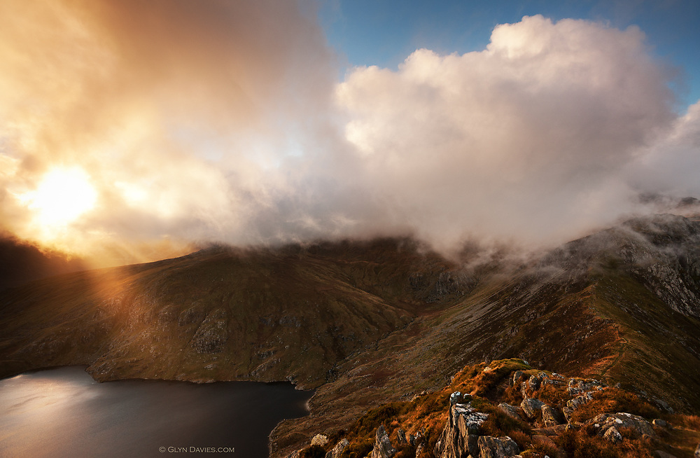 Sunshine burning through huge masses of low hill cloud swirling over the Welsh Carneddau mountains of Northern Snowdonia and lake Llyn Ffynnon Llugwy below. Taken from Y Braich mountain