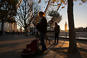 Musician Conor Scott busking with sun setting on the Southbank riverside walkway, London, United Kingdom. The South Bank is a significant arts and entertainment district, and home to an endless list of activities for Londoners, visitors and tourists alike.