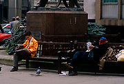 A trader from the LIFFE futures exchange takes a break in the street during a weekday lunchtime. Alongside him on another bench is a homeless man in the City of London in a scene of wealth with prosperity versus the fate of poverty and loss. Wearing the orange jacket of this once thriving financial instutution, we see a scene of wealth and prosperity, from an era of growth during the industrial revolution to the arrogance and self-indulgence during the government of John Major - a political inheritance from Margaret Thatcher. The LIFFE exchange was synonymous with Thatcherite capitalist money-making ethos in the City of London of the 80s and early 90s before the takeover by Euronext in January 2002. It is currently known as Euronext.liffe. Euronext subsequently merged with New York Stock Exchange in April 2007.
