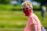 Confusion over masks remains to be clarified, as an older lady , apparentltly, pontlessly wears a mask on her outdoor walk. Fit older people make their own decision on whether to stay locked down - All ages enjoy the opportunity to exercise on Wimbeldon Common as the sun is out. The 'lockdown' continues for the Coronavirus (Covid 19) outbreak in London.