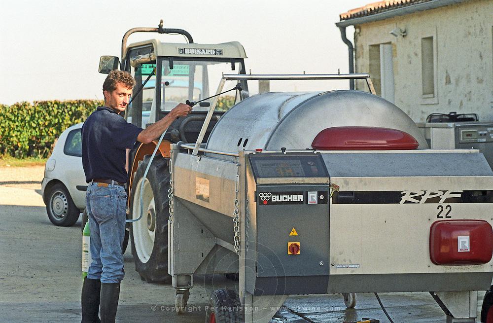 Cleaning a pneumatic press. Chateau Sansonnet, Saint Emilion, Bordeaux, France