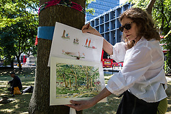 London, UK. 26th June, 2018. Local resident Primavera Boman-Behram holds images of trees in Euston Square Gardens and construction workers on site as part of a protest using art against the planned felling by HS2 Ltd of mature London Plane, Red Oak, Common Lime, Common Whitebeam and Wild Service trees to make way for temporary sites for construction vehicles and a displaced taxi rank as part of preparations for the HS2 high-speed rail line. The protest, involving the capturing of images of the trees on paper using a variety of different techniques, was hosted by the artist Dan Llywelyn Hall as 'The Last Stand Against the Environmental Damage of HS2'.