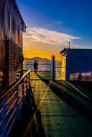 Passenger aboard Hurtigruten ship MS Vesteralen enjoying the scenery on deck , near Alesund, Norway.