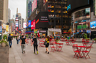 New York, NY, USA -- June 8, 2015. Tourists walk through a pedestrian plaza in midtown heading for Times Square.