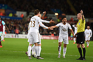 The Swansea city players crowd around referee Lee Mason as they appeal for a penalty after the ball had appeared to hit the arm of West Ham defender James Collins who blocked a shot from Ki Sung-Yueng of Swansea city .Barclays Premier league match, Swansea city v West Ham Utd at the Liberty Stadium in Swansea, South Wales  on Sunday 20th December 2015.<br /> pic by  Andrew Orchard, Andrew Orchard sports photography.